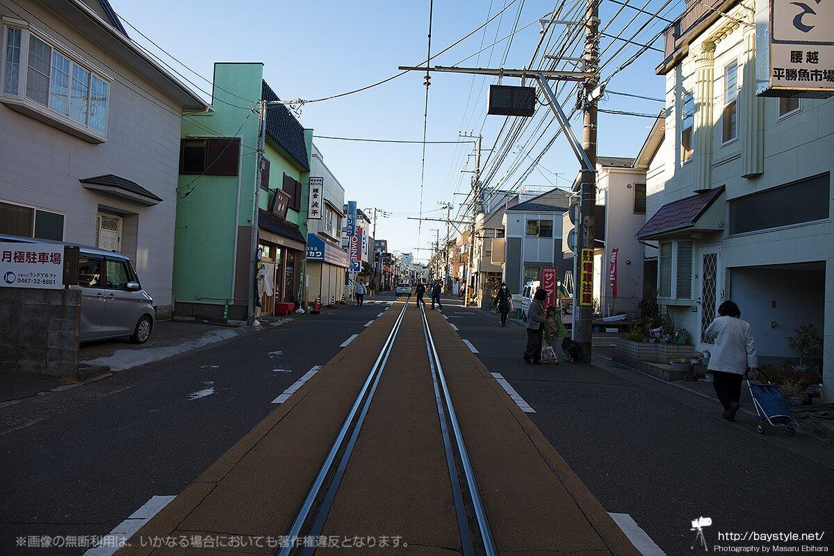 線路をまたいで渡る人々と通過する車