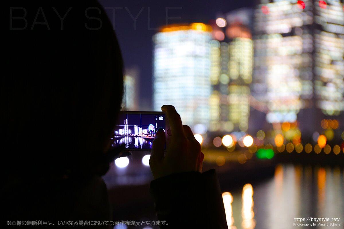 横浜みなとみらいの綺麗な夜景を撮影する女性