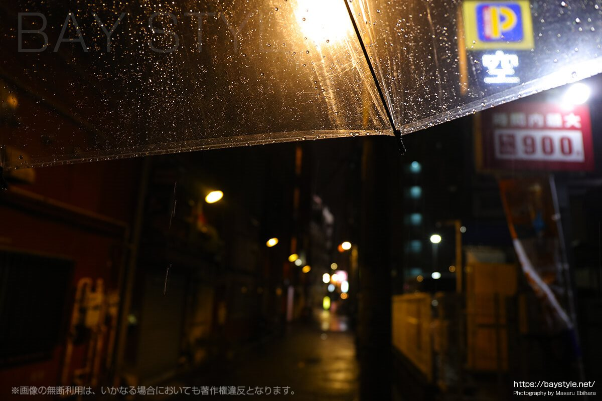 傘から落下する雫を撮影しながら、街の灯りを玉ボケ撮影