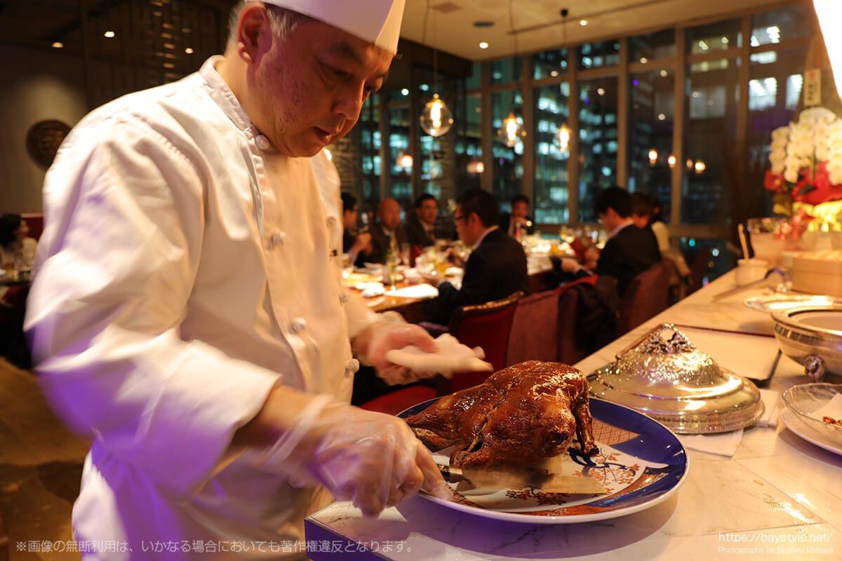 北京ダックをさばく料理長の佐藤さん