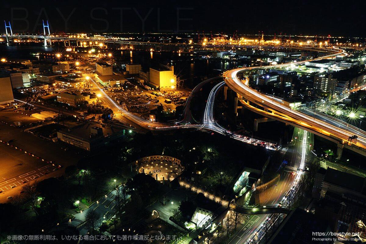 首都高速湾岸線とブルーにライトアップしたベイブリッジ