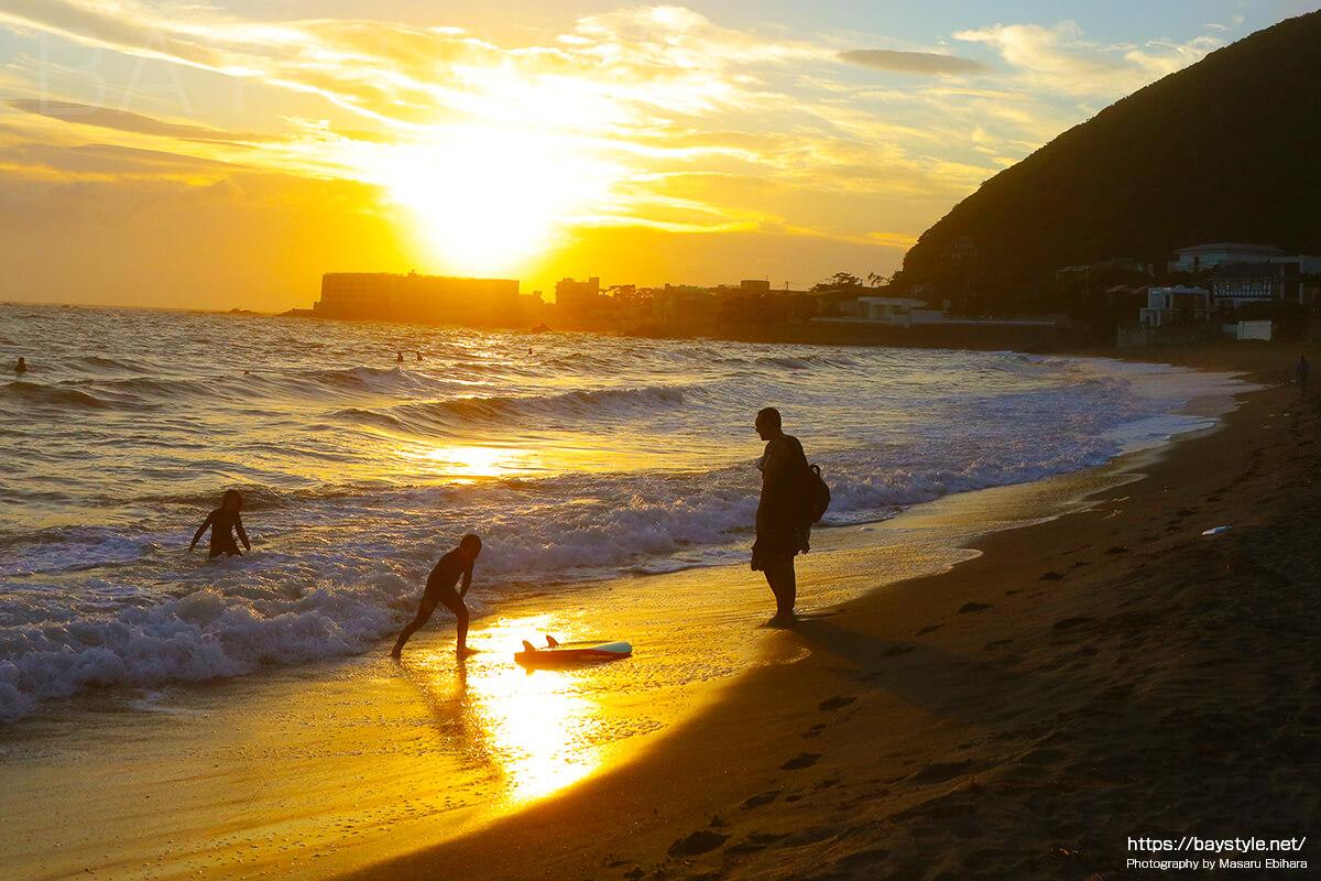 夕暮れの親子と波打ち際に続く足跡