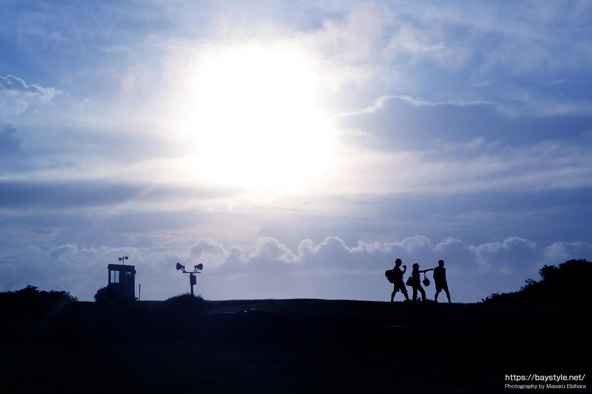 丘の上を歩く人のシルエット